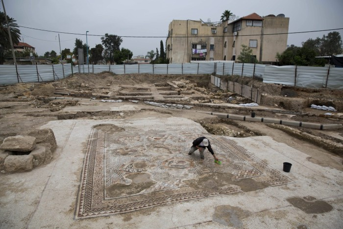An employee of Israel's antiquities authority works on a 1,700-year-old Roman-era mosaic floor in Lod, Israel, Monday, Nov. 16, 2015. Archaeologists found the mosaic last year while building a visitors' center meant to display another mosaic, discovered two decades earlier at the same spot. The authority said the newly discovered Roman-era mosaic measures 11 meters by 13 meters (36 feet by 42 feet) and paved the courtyard of a villa in an affluent neighborhood that stood during the Roman and Byzantine eras. (AP Photo/Ariel Schalit)