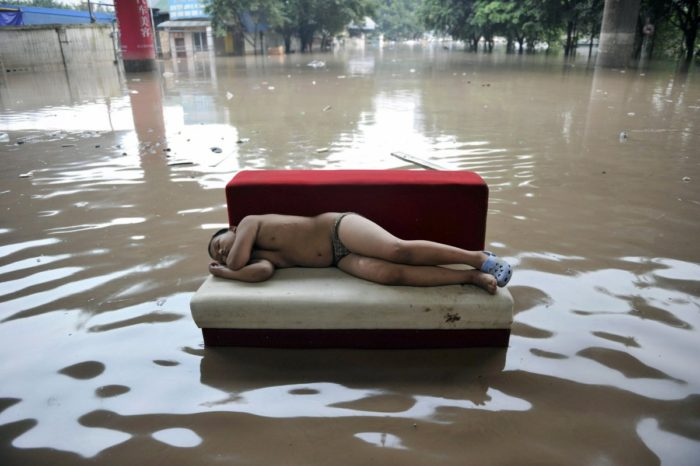 Here, a child sleeps in the middle of a flooded street in China's Chongqing municipality during a 2010 outbreak of torrential rain, which killed dozens of people.