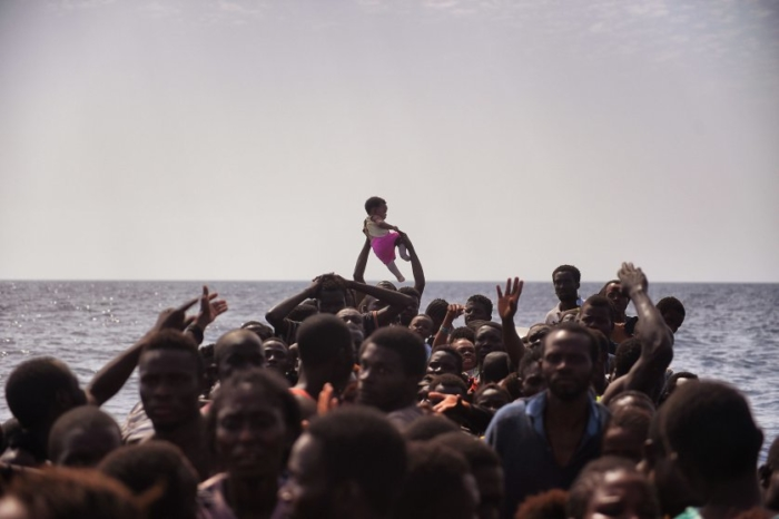 Migrants wait to be rescued by members of Proactiva Open Arms NGO in the Mediterranean Sea, some 12 nautical miles north of Libya, on October 4, 2016. At least 1,800 migrants were rescued off the Libyan coast, the Italian coastguard announced, adding that similar operations were underway around 15 other overloaded vessels.